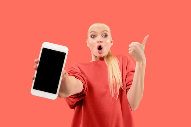 Retrato de una niña sorprendida, sonriente, feliz y asombrada que muestra el teléfono móvil de pantalla en blanco aislado sobre fondo coral.