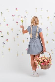 Retrato niña sosteniendo la cesta con flores