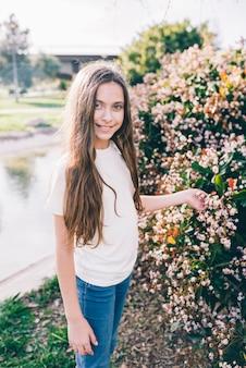 Retrato de una niña sosteniendo flores en la planta en el parque