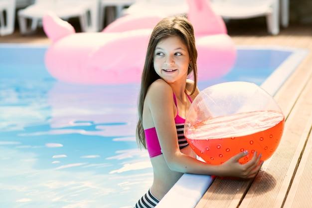 Retrato de niña sosteniendo una pelota de playa mirando a otro lado