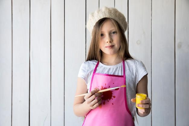 Retrato de una niña sosteniendo un pincel y una botella de pintura amarilla en la mano de pie contra la pared de madera blanca