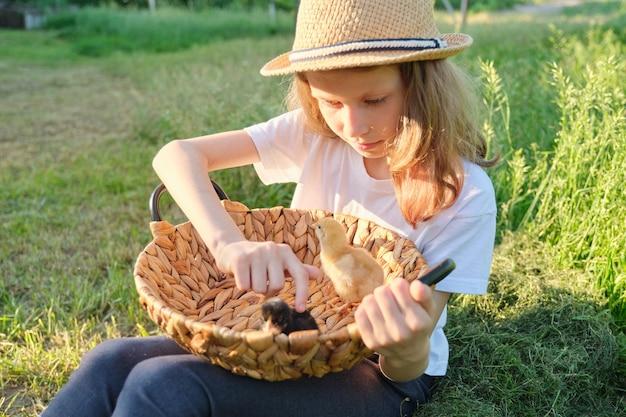 Retrato de niña sosteniendo pollitos recién nacidos en la canasta, día soleado de primavera en el jardín