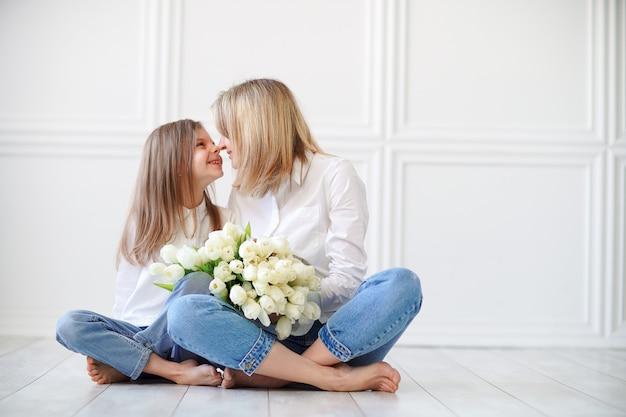 Retrato de niña y su madre con tulipanes blancos