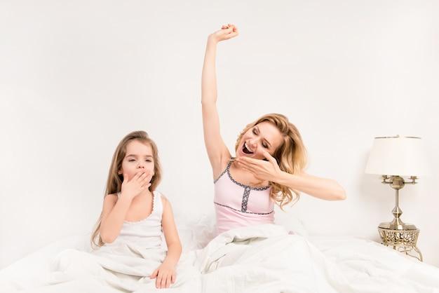 Retrato de niña y su mamá despertando por la mañana