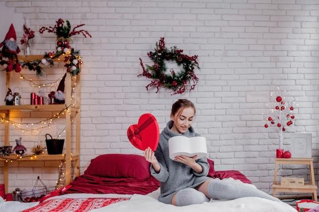 Retrato de una niña en un suéter gris con una caja de regalo roja en forma de corazón sentado en el apartamento, concepto de san valentín, espacio de copia