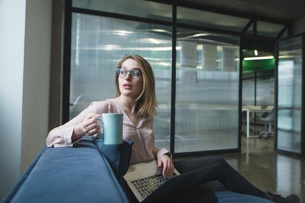 Retrato de una niña con una taza de café en sus manos y una computadora portátil