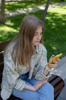 Retrato de una niña con teléfono inteligente en sus manos ella lee chats de correo electrónico en las redes sociales con amigos