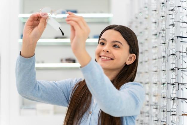 Retrato de niña en la tienda de anteojos eligiendo par