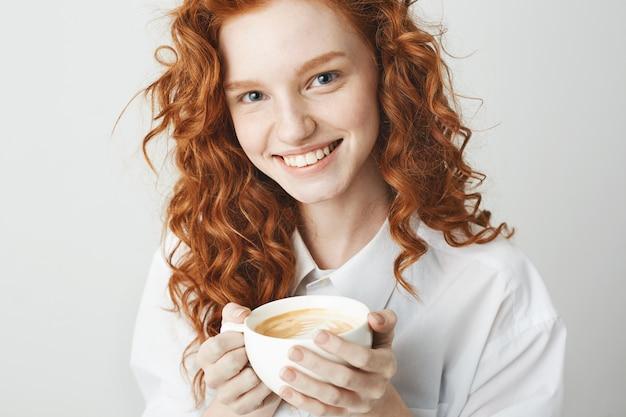 Retrato de niña tierna pelirroja con pecas sonriendo sosteniendo la taza