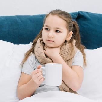 Retrato de una niña tocando su garganta sosteniendo una taza de café en la mano