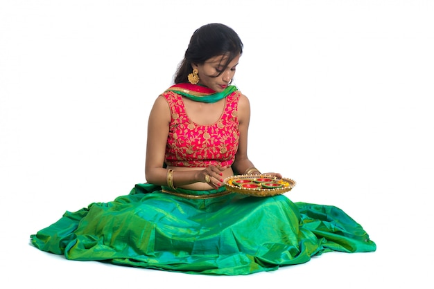 Retrato de una niña tradicional india sosteniendo diya, niña celebrando diwali o deepavali con la celebración de la lámpara de aceite durante el festival de la luz sobre la superficie blanca