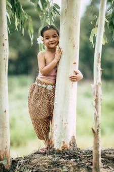 Retrato de niña en traje tradicional tailandés y poner flor blanca en su oreja, pararse y abrazar el tronco del árbol, sonreír, copie el espacio