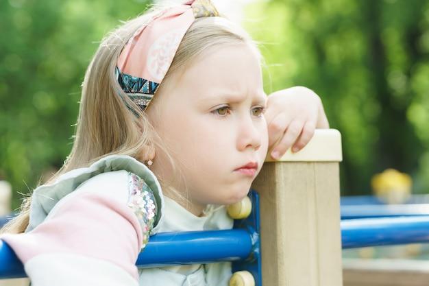 Retrato de niña triste y aburrida en un parque de la ciudad