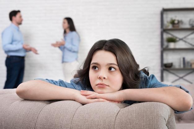 Retrato de niña triste con padres discutiendo detrás