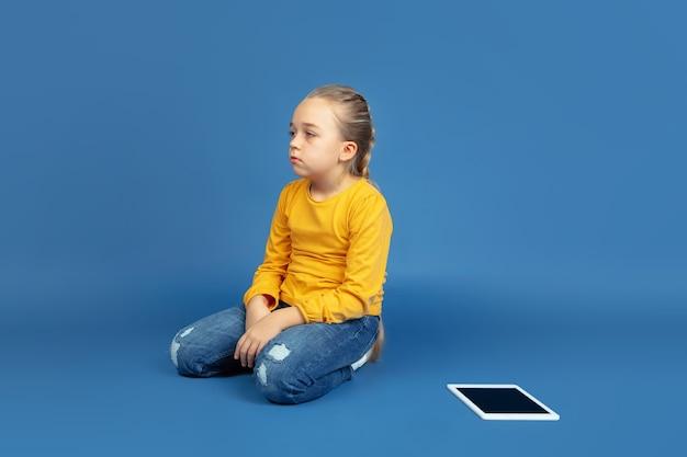 Retrato de niña triste sentada aislada sobre fondo azul de estudio. cómo se siente ser autista. problemas modernos, nueva visión de los problemas sociales. concepto de autismo, infancia, salud, medicina.
