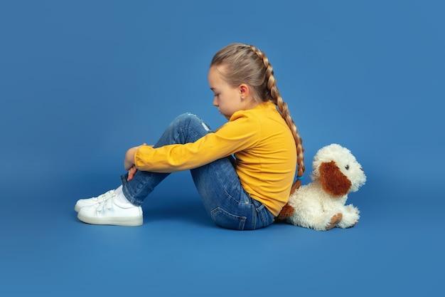 Retrato de niña triste sentada aislada sobre fondo azul.