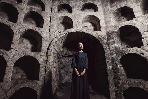 Retrato de una niña con un vestido negro con un cuello blanco de pie en una abertura de piedra