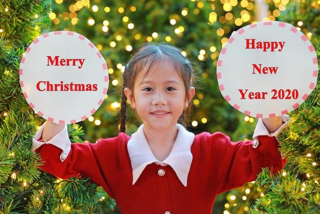 Retrato de niña en vestido rojo con etiqueta de círculo con texto feliz navidad y feliz año nuevo 2020 en festival de temporada de invierno contra el fondo del árbol de pino.