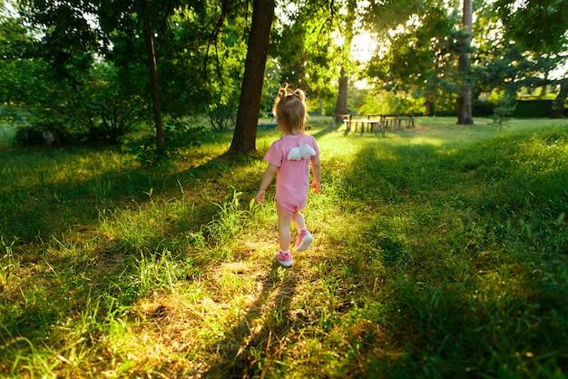 Retrato de una niña en vestido rosa caminando en el parque verde en un día soleado.