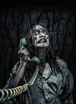 Retrato de la niña zombie de terror llamando por teléfono. aterrador
