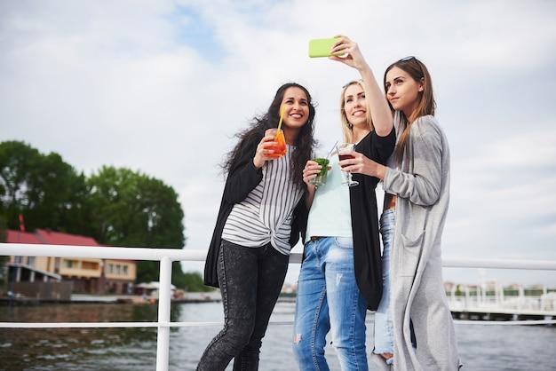 Retrato de niñas felices en el muelle en el lago.
