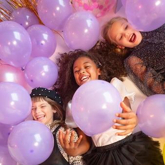Retrato, niñas jóvenes, en, fiesta, con, globos