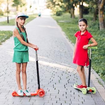 Retrato de niñas de pie en patinete scooter en el parque
