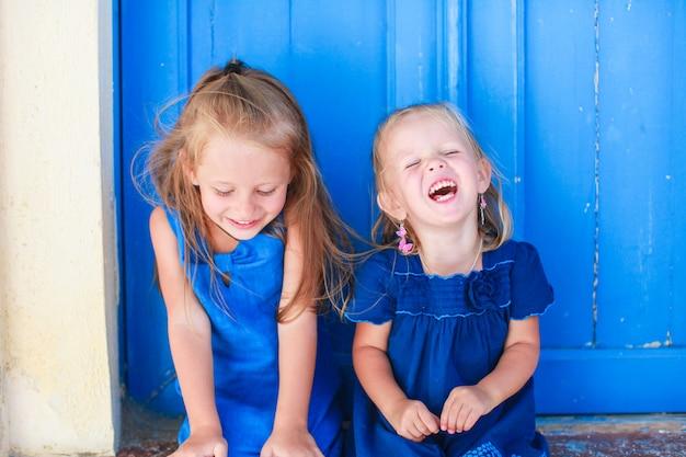 Retrato de niñas sonrientes sentado cerca de la antigua puerta azul en el pueblo griego, emporio, santorini