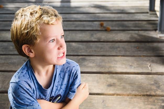 Retrato de niño de 6 años con expresión en su rostro con ira y sorpresa.