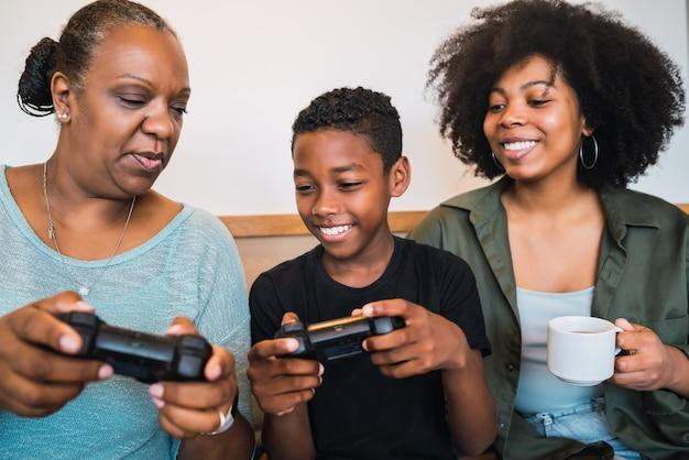 Retrato de niño afroamericano enseñando a la abuela y a la madre cómo usar el joystick para jugar videojuegos