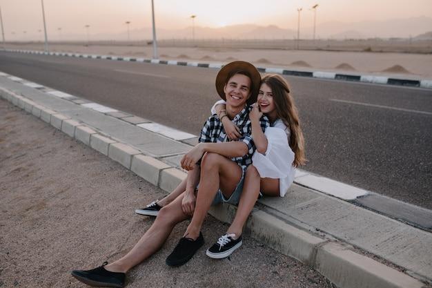 Retrato de niño alegre y mujer de pelo largo en pantalones cortos de mezclilla divirtiéndose afuera, descansando en la carretera y disfruta del atardecer. linda mujer joven sonriente abrazando a su novio, mientras posa después de caminar