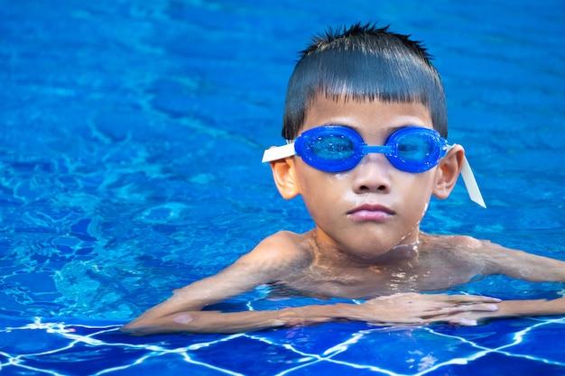 Retrato de niño asiático, gafas azules y flotando en la esquina de la piscina y el agua azul refrescante