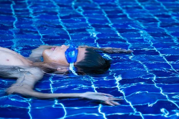 Retrato de niño asiático ware un azul gafas, tendido en la piscina y agua refrescante azul, azulejo