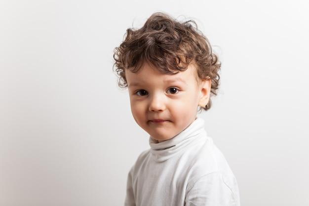 Retrato de un niño audaz con el pelo rizado de tres años en un blanco aislado