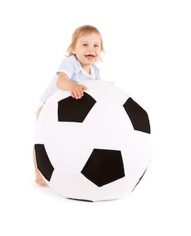 Retrato de niño con balón de fútbol sobre pared blanca