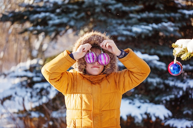Retrato de un niño con bola de navidad caminando en la naturaleza de invierno. jugando con nieve. concepto de infancia feliz.