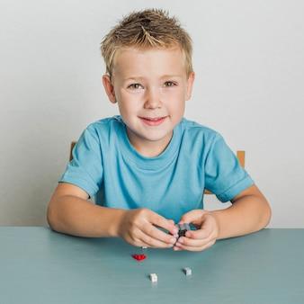 Retrato de niño de cabello rubio con lego