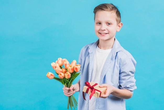Retrato de un niño con caja de regalo envuelta y tulipanes en la mano contra el fondo azul