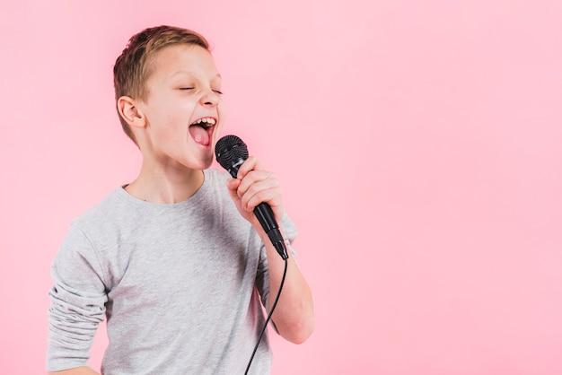 Retrato de un niño cantando canción en el micrófono contra el fondo de color rosa