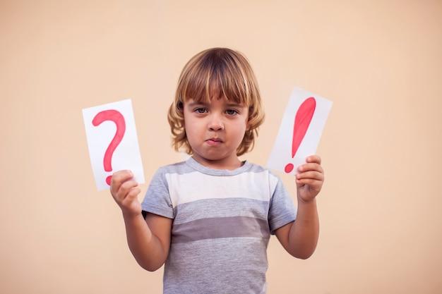 Retrato de niño chico sosteniendo tarjetas con signo de exclamación y signo de interrogación. concepto de niños y educación
