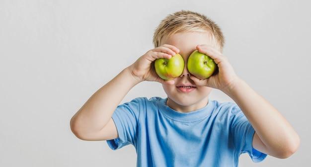 Retrato de niño divertido con manzanas