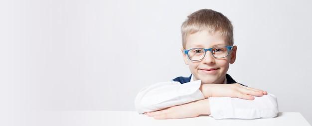 Retrato de un niño emocional. un niño de escuela sonríe con hoyuelos, feliz de regresar a la escuela. texto sin formato. banner con espacio de copia.