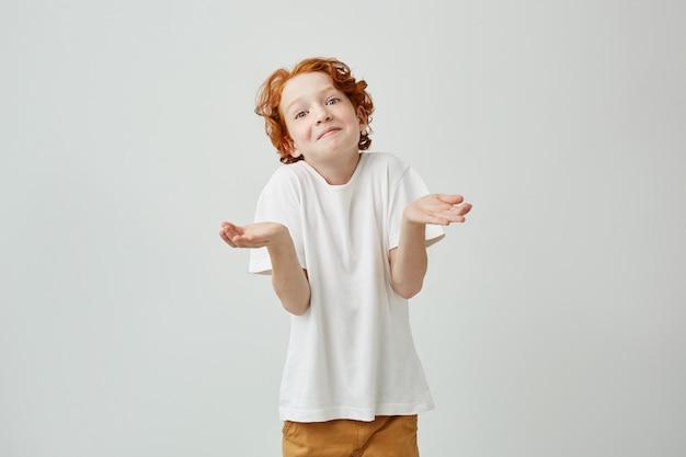 Retrato de niño encantador con el pelo rojo brillante gesticulando con las manos mostrando la respuesta de no sabe a la pregunta del maestro.