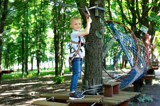 Retrato de un niño en equipo de escalada en un parque de cuerdas, sosteniendo una cuerda con una carabina.