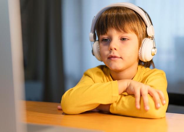 Retrato de niño de escuela en camiseta amarilla tomando clases virtuales