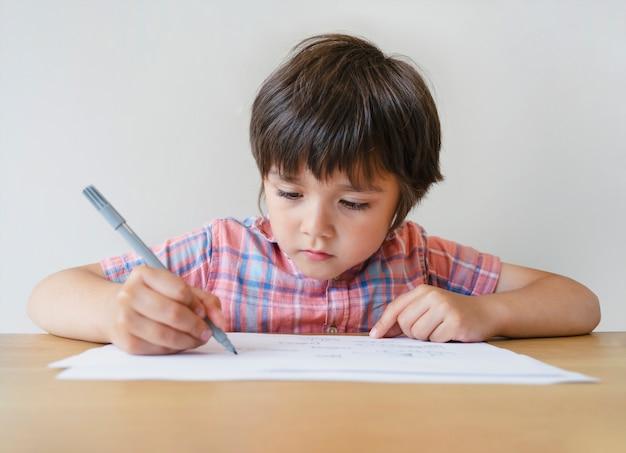 Retrato de niño de escuela niño sentado solo haciendo los deberes