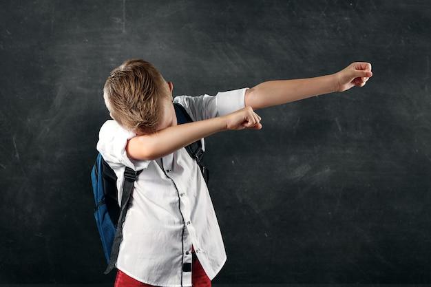 Retrato de un niño de una escuela primaria sobre un fondo de una junta escolar