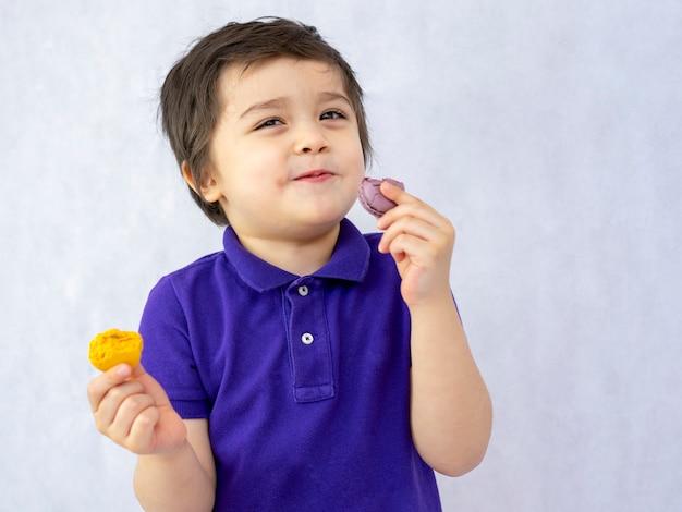 Retrato de un niño feliz comiendo macarons