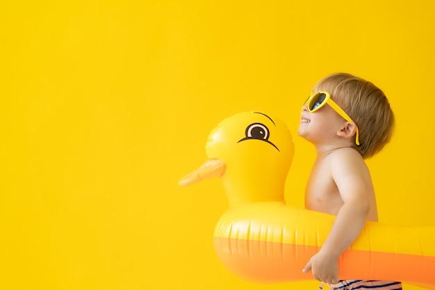 Retrato de niño feliz contra la pared amarilla en vacaciones de verano.