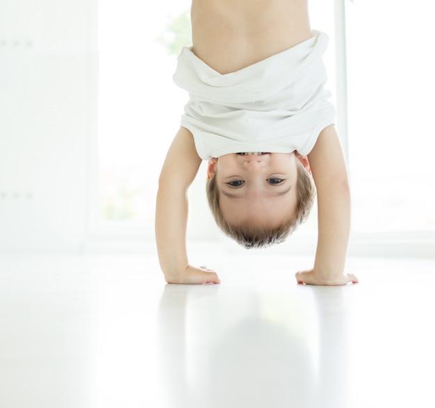 Retrato de niño feliz jugando boca abajo en el interior en la sala de estar en el piso blanco caminando en las manos